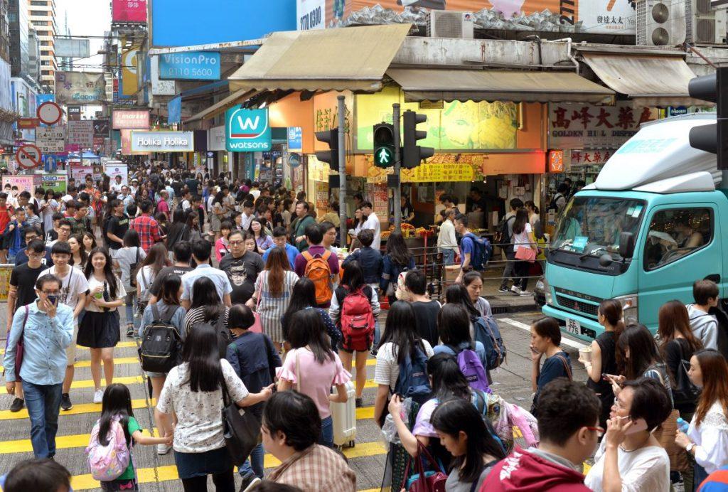 People walking across a busy traffic crossing.