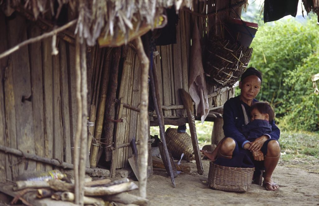 A person sits outside a wooden house.