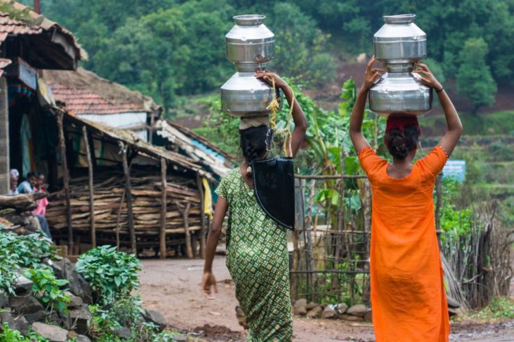 Women carrying containers of water above their heads