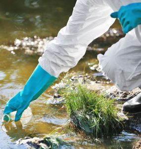 An environmental scientist's gloved hand reaches into water