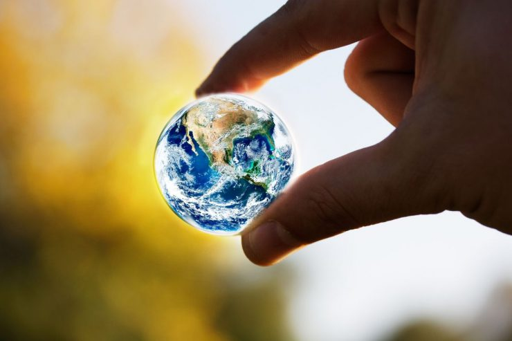 A marble-sized Earth held between a thumb and finger