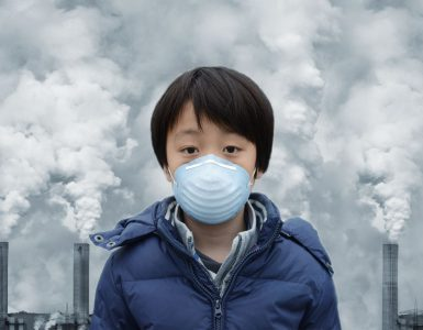 A child with a face mask standing in front of a row of chimneys with smoke rising from them