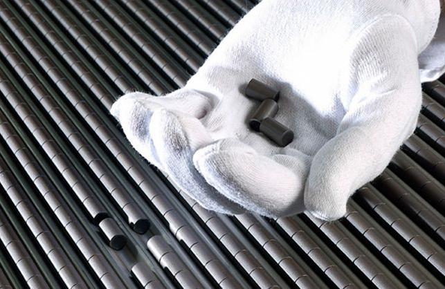 gloved hand holding uranium dioxide pellets