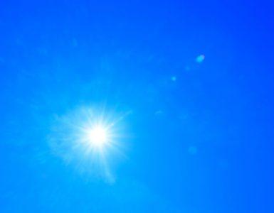 light from the sun against a blue sky