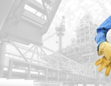 An apprentice's overalls, gloves and hard hat can be seen in front of an offshore platform.
