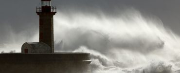 Spray from a wave is blown over a lighthouse on the coast