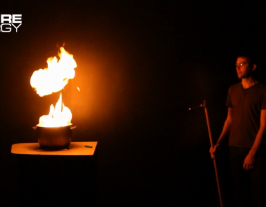 A science presenter safely observes the burning of a fuel