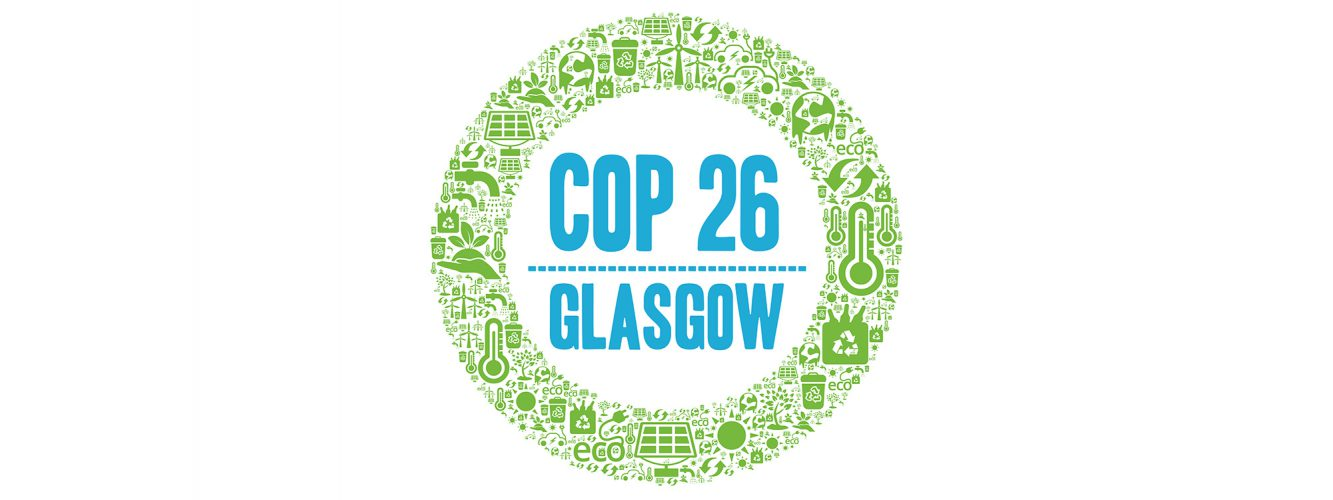 """An illustration shows a green circle comprised of icons of sustainability. A blue title in the middle of the circle reads, """"COP 26 Glasgow""""."""